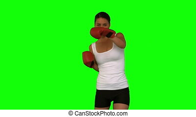 Woman boxing against a green screen