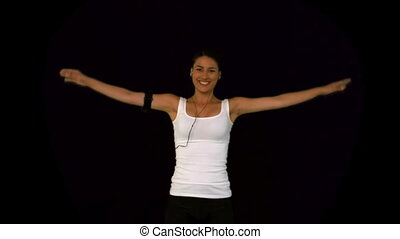 Attractive woman doing exercise against a black background