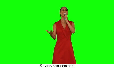 Attractive woman singing against a green screen