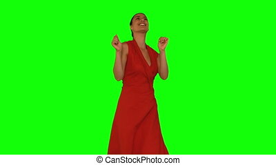 Smiling woman dancing against a green screen