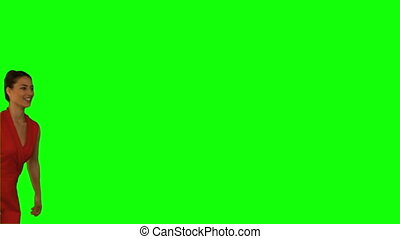 Elegant woman jumping against a green screen