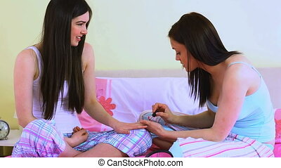 Woman applying nail polish on her friends nails in bedroom