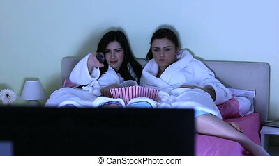 Cheerful friends watching movie together lying on the bed