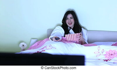 Cheerful young woman watching TV