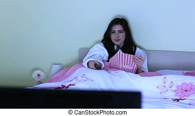 Young woman watching horror movie alone in her bedroom