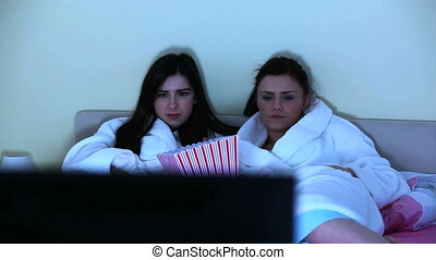 Young women watching horror movie together lying on bed