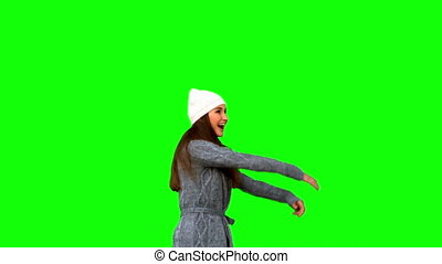Smiling young woman cheering on green background