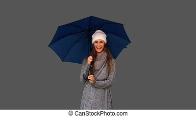 Pretty young woman playing with umbrella on grey background