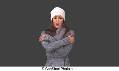 Cold cute young woman shivering on grey background