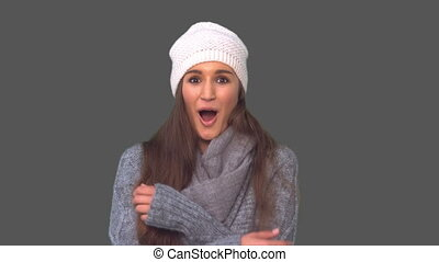 Cold casual young woman shivering on grey background