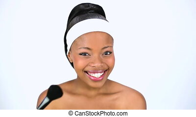 Attractive woman applying blusher while posing on white...