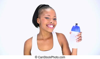 Smiling model in sportswear holding flask posing on white...