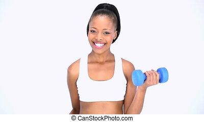 Cheerful model in sportswear exercising with dumbbells while...