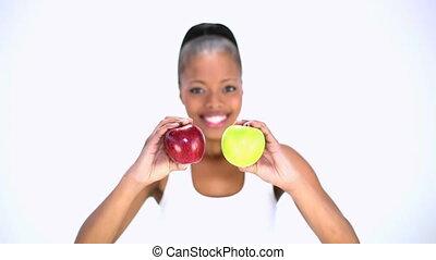 Smiling model holding apples posing on white background