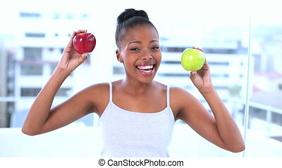 Cheerful beautiful model holding apples smiling at camera