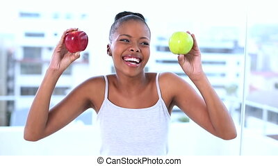 Cheerful natural model holding apples smiling at camera