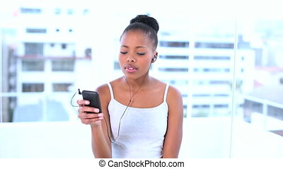Thoughtful natural model enjoying music in her smartphone