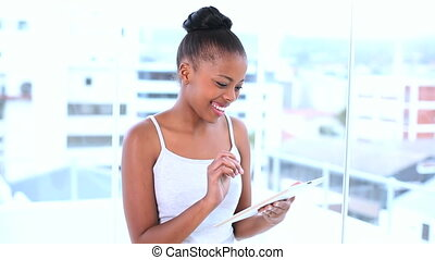Smiling natural model using her tablet computer while posing