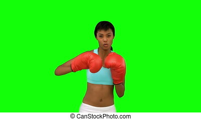 Attractive model with red gloves boxing on green background
