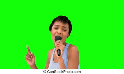 Attractive model singing on mike on green background