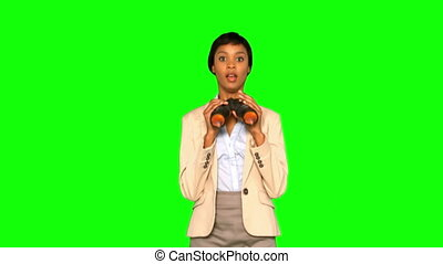 Curious businesswoman with binoculars jumping on green...