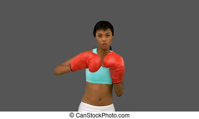 Gorgeous woman with red gloves boxing on grey background