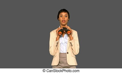 Concentrated businesswoman jumping while holding binoculars...