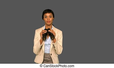 Businesswoman jumping while holding binoculars on grey...