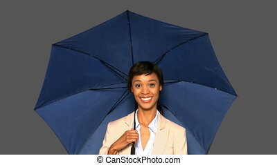 Happy businesswoman with umbrella on grey background