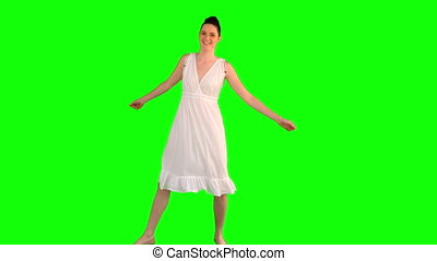 Cheerful model in white dress dancing on green background