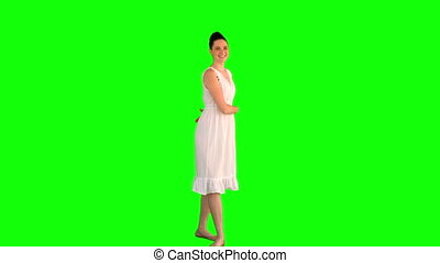 Cheerful model in white dress turning round on green...