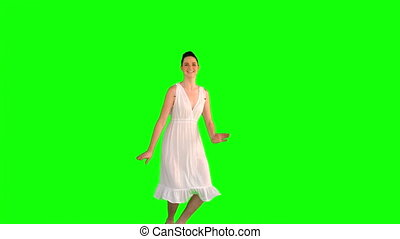 Cheerful model in white dress jumping on green background