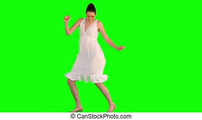 Happy model in white dress dancing on green background