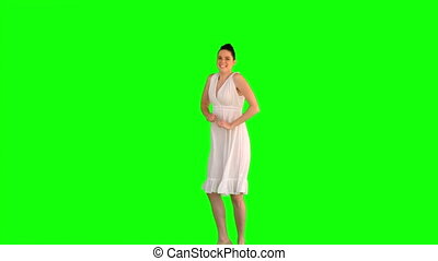 Energetic model in white dress jumping on green background