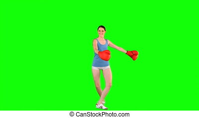 Energetic model with boxing gloves turning round on green...