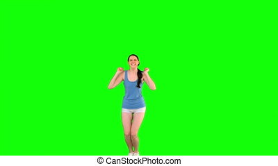 Energetic young model in sportswear jumping on green...
