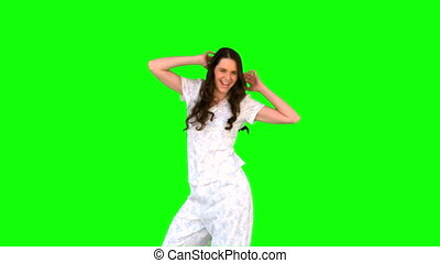 Energetic young model in pyjamas dancing on green background