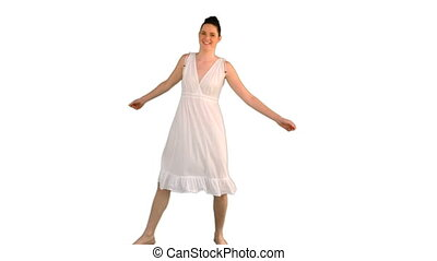 Beautiful model in white dress dancing on white background
