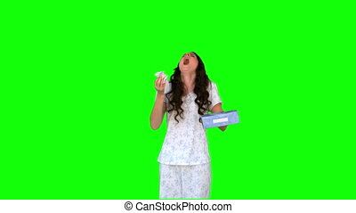 Sick young model in pyjamas sneezing on green background