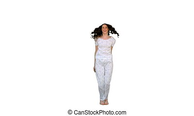 Cheerful young woman in pyjamas exercising on white...