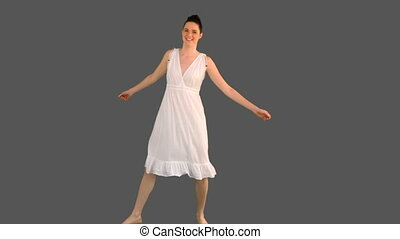Elegant woman in white dress dancing on grey background