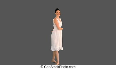 Elegant woman in white dress turning round on grey...