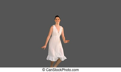 Elegant woman in white dress jumping on grey background