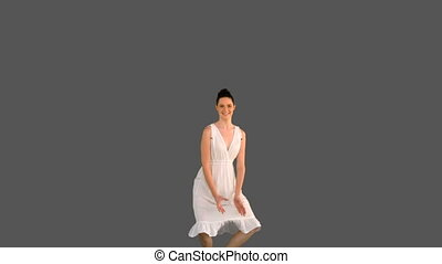 Elegant young woman in white dress jumping on grey...