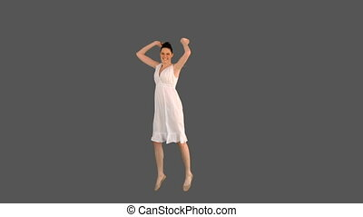 Elegant young model in white dress jumping on grey...