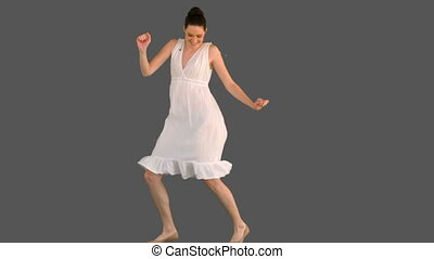 Elegant young woman in white dress dancing on grey...