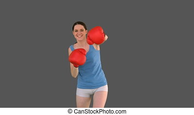 Pretty young model with boxing gloves punching on grey...