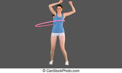 Young model in sportswear doing hula hoop on grey background