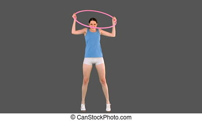 Young model in sportswear playing with hula hoop on grey...