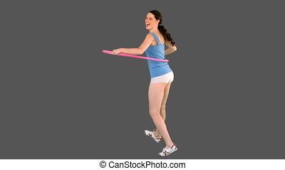 Young model in sportswear exercising with hula hoop on grey...